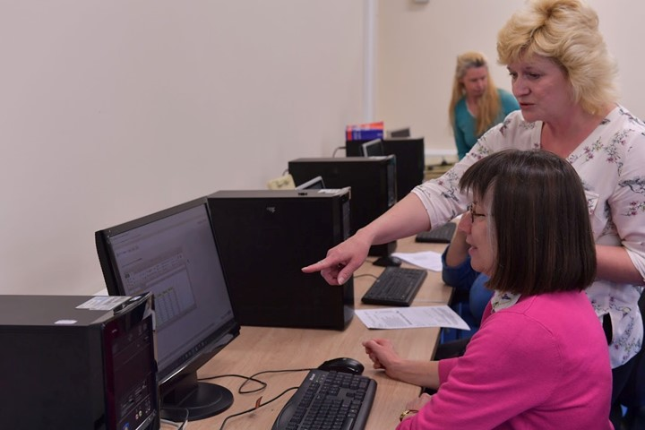 Teacher Pointing To Computer As She Helps Student